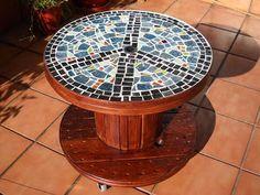 Una bobina barnizada, unas ruedas en su base y un mosaico en la superficie y tendrás una mesa única.