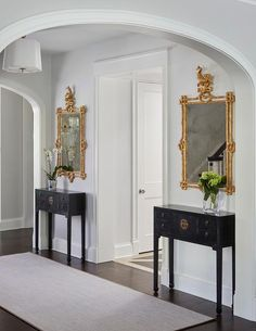 An arch doorway leads to a gorgeous foyer boasting a gray rug placed in front of black chinoiserie console tables fixed on either side of a doorway beneath gold gilt mirrors illuminated by a Barbara Barry Simple Scallop Pendant.