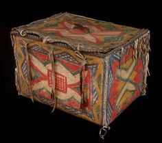 "Sioux Parfleche Box, 1890 The parfleche box is lined with an interior wooden frame. Decorating the outsides is a series of multi-colored curvilinear rawhide panels outlined in black. The lid is trimmed with blue stroud cloth and fastened with quilled drops. Fringe accents the edges of the box; 9.5"" tall; 14.5"" long; 10.5 deep."