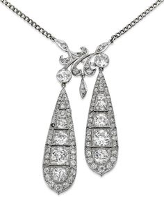A diamond pendant.  Converted from a pair of early 20th century diamond pendent earrings, the highly articulated pearshaped drops each set with a graduated row of old round brilliant-cut diamonds, with similarly-cut diamond-set surround, and with a diamond-set foliate scroll surmount, all suspended from a curb-link chain, chain length 31cm, pendant length 60mm, one diamond deficient, the diamonds estimated to weigh approximately 8.20cts in total