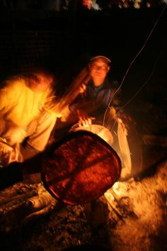 Shaman's drum heated over fire.