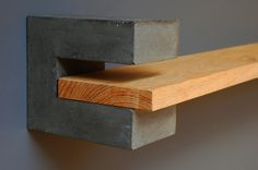 A pair of shelf brackets made from dark grey concrete. Hand made and cast and polished to a smooth finish.  Included is an oak shelf designed to sit with a pair of our concrete shelf brackets. Untreated solid oak shelving, planed and hand finished. Double click on the large image to se
