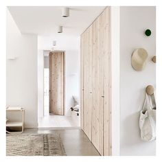 Natural wood doors warm up all white minimalistic interiors in this lovely home.  Photo by Petra Bindel for Swedish Elle Decoration #elledecor #swedishstyle #interiors #anoteonstyle