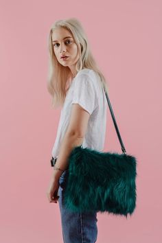 DESCRIPTION The Ziggy is made from long pile emerald green faux fur. This style features a zipped interior pocket and embossed logo. The metallic...