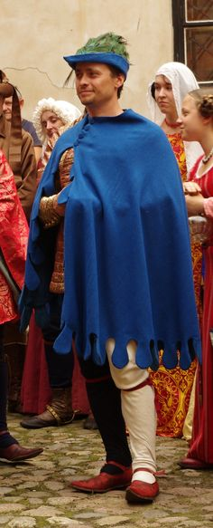 14th Cent: Wool bycocket festooned with peacock feathers, wool cloak (dagged), over brocade purpoint/cotehardie