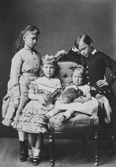 Da esquerda para a direita: Princesa Irene de Hesse, de pé; Princesa Alix de Hesse, de pé; Princesa Marie de Hesse, sentada, com o que parece um coelho no colo; Príncipe Ernesto Luis de Hesse, de pé. Maio de 1876.