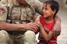 A member of Iraqi forces gives juice to a child in the village of Umm Mahahir, south of Mosul, on October 28, 2016 after troops recaptured it from the Islamic State (IS) group jihadists as part of their operation to retake the main hub city of Mosul....