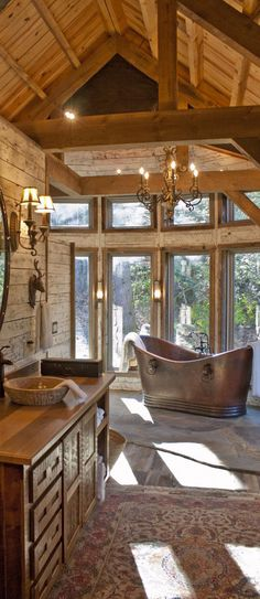 Rustic bathroom with stunning copper tub designed by Pearson Design Group #logcabins #rustichomes #ranchhomes #rusticbedroom #rusticbedroomideas #loghomelivingrooms #greatrooms #rusticgreatrooms #loghomegreatrooms