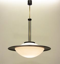 A large and rare 1960s Italian space-age ceiling fixture by Stilnovo.   With matt glass inner diffuser, contoured outer ring, brass stem and black ceiling rose, the components create a striking modernist form.   This large fixture illuminates a wide area. The thick glass casts a warm, diffused light.   It is in good, rewired condition. The neck of the glass shade has minor restoration, not visible when the lamp is assembled.