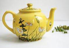 yellow teapot in brown betty shape decorated w/ daisies and grass leaves, ceramic