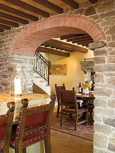 Love the stone walls, brick arch, chairs and table, railing on the staircase, fireplace in the dining area.