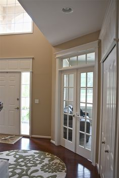 I just want the doors to look like they have a purpose other than just an opening with cheap trim.Hire a Detail Carpenter to install moldings above each door. Even though the moldings are varying sizes, it creates the illusion that the doors are all the same height. also add a transom window above the french doors. Symmetry, character, architectural interest.