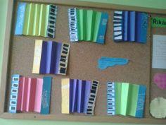 """Akordeony - harmonika z barevného papíru, po stranách tvrdý barevný papír a bílé knoflíky jsou """"odpad"""" z děrovačky"""