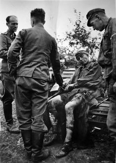 A rare moment of humanity in a war of extermination: Doctors of 5. Waffen SS Division Viking attend to a seriously wounded Russian POW. Note the large open wound on the Russian's left thigh. One of the doctors is taking the Russian's pulse. Hopefully, he was operated on. Undated, undisclosed location.