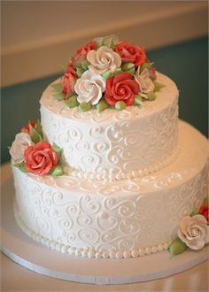 An elegant two tier wedding cake with orange and white sugared flowers to add that splash of colour