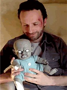 Andrew Lincoln plays with a zombie baby doll. (this will be Judith)...