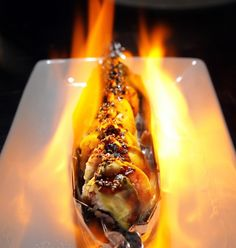 MMMMM..  Oh My God sushi roll complete with flames as served at Tani Sushi Bistro in Clayton. The roll contains shrimp, crab and avocado as well as sweet and spicy sauce and a little mayo.