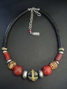 by Luda Hunter | Choker necklace; antique trade beads with the centre bead being a rare antique King glass bead, 2 large antique Venetian red cornaline d'aleppo round and cylinder beads, Ethiopian coin silver beads and old African Vulcanite heishi beads. | 160$