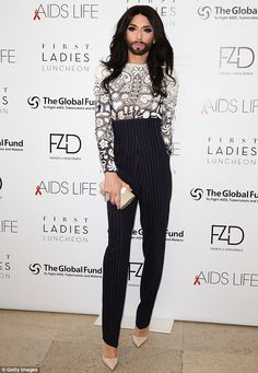 Cowell would approve! Conchita Wurst wears a pair of high waist chalk stripe trousers at t...