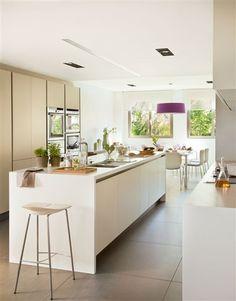 Una amplia cocina con mobiliario lacado, dándole un toque de color la lámpara de techo.