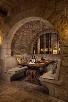 Stone & brick wine cellar in Romanesque style home :: love the arched stone booth...