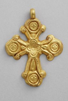 A gold leaf encolpion (religious pendant containing sometimes religious relics) in the shape of an aniconic cross, elegantly decorated on one side. The arms are treated like flowering plant stems surrounding small crosses inscribed in medallions. A double edged cross is in the center.  6th cent . Byzantine