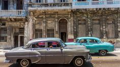 Cuba cars Malecon — Old cars pass buildings falling apart near the Malecon in Havana. Cuba is truly a place 'frozen in time.