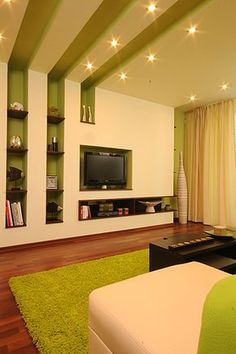 Trendy false ceiling design that conivues as wall shelf. Very well lit. Smat color n design for modern homes
