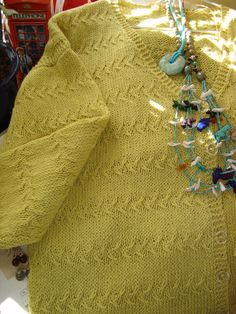 """This is a very pretty stitch pattern on this women's cardigan. It is called """"wheat sheaf"""" as the subtle pattern resembles sheafs of wheat standing in a field. The knitting pattern is for a DK yarn and is available to knit in sizes Small to XL."""