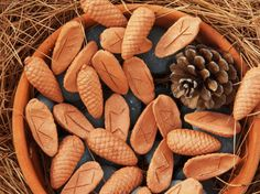 """Large Pine Cone Ceramic Futhark Set of Runes by Maid of Earth Studio. These Ceramic Pine Cone Runes are beautifully hand made from micaceous red clay from the Manzano Mountains in New Mexico. The ancient Pagan symbol of the pine cone is """"Eternal Life."""" The mica shimmer in these runes will remind you to respect nature all around you and respect each other through the Oracle."""