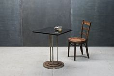 USA, c.1930s. Ranko Engine Company of NYC Manufactured this Art Deco Influenced Cafe Table. Black Micarta Top, Heavy and Over Built, with Cast Iron Stepped Base, Three Steel Pole Supports, Cast Iron Connection Plates.