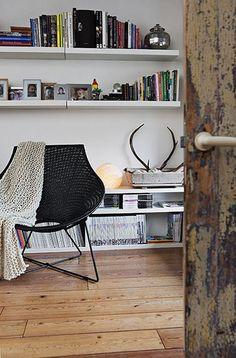 floor, black chair, white walls, books