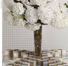 Escort Card Display  The lattice design of the mirrored tabletop inspired the graphic layout of these contrasting gold and silver escort cards. A cloud of white hydrangeas and a vase filled with contrasting gold pebbles creates a high centerpiece.    Two-...