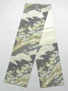 This is a graceful Fukuro obi with flying crane and flower such as 'kiku'(chrysanthemum) and clematis on bamboo fence pattern, which is woven