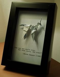 A handmade origami unicorn in the style of that seen in Ridley Scotts Blade Runner, mounted in a 10x15cm (4x6) box frame with a quote from the film hand typed underneath. Perfect for any fan!  QUOTES  The standard quote that accompanies the unicorn is the last line of the film (Directors Cut, for you pernickety few out there!), spoken by Edward James Olmos Detective Gaff, the man who folds the unicorn in the film: Too bad she wont live. But then again, who does?  If you would prefer…