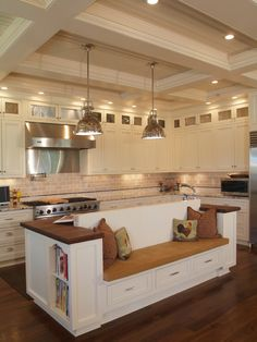 I adore the island with built-in bench seat (for possible banquette seating?) in this kitchen! It is so unique! I also love the beautiful cabinetry, coffered ceiling, high-end stainless steel appliances and vent hood.