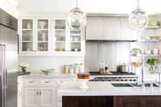 white cabinets, wood island cabinets, globe pendants, arched stainless hood, slab backsplash