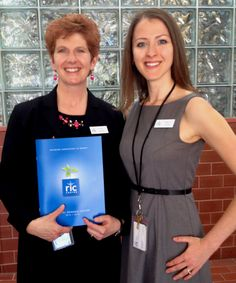 Executive Director Pam Banks (left) and Operations Coordinator Mariya Leslie (right) pose with the RIC Centre's 2014 Annual General Report, proudly designed by Blade.