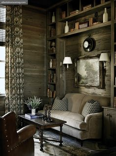 Love this woodland-inspired room.  The wood paneling on the wall, the dark modern cabin feel . . .