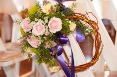 Chair maker wreath with spray roses, mini carnations,novelty daisies,queen Anne's lace,wax flower, greenery with a purple accent ribbon. Re purposed for reception table centerpiece.  Flowers by Bloom and Leaf Event Florist.  Photo by Tim Malkemus Photography.
