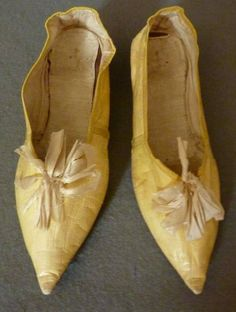 Slippers: ca. 1790's, kid, silk looped ribbon decoration, the top edge and the back seam all bound with silk ribbon, low shaped leather heels, leather soles, insides of slightly glazed linen.