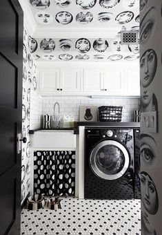 Commanding wallpaper from Lee Jofa sets the tone for the black-and-white laundry room. Classic hexagonal tiles cover the floor, while polka dots play under the sink.