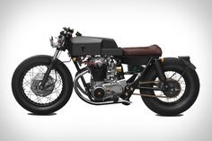 Thrive Yamaha XS650 Motorcycle. Based on a classic 1968 Yamaha XS650, this updated version features a spartan color scheme of black, grey, brass, and brown, a completely overhauled engine, hand-fabricated custom bodywork, a slightly lowered front end, a pair of leather belts under the battery box for holding a shirt or jacket, and even a custom bag containing all the tools needed to maintain the bike.