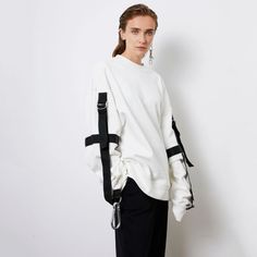 Simple yet suave, this white pullover sweatshirt is truly urbane in every sense of the word. In a brow-raising twist, it has an alluring army uniform aesthetic in its hooked suspender detailing on the sleeves.