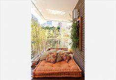O tatame, feito de deque de cumaru, recebe o futon e as almofadas para compor o espaço destinado ao descanso. Atrás dele, na esquina da varanda, a floreira canelada forma o L, onde ficam os bambus altos, que garantem a privacidade dos moradores