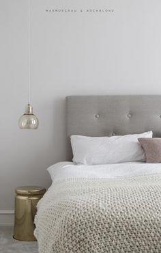 Schlafzimmer Inspiration mit Boxspringbett in Grau und cremefarbenen Akzenten.