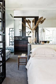 Dark wood and tile bath behind mirrored wall in South African home; Lucien d'Avice