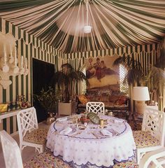 In the dining room of Valentino's home in Rome—photographed here in 1974—the designer created an exotic feeling by tenting the space in a broad striped fabric.