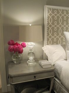 Monochromatic gray bedroom design with soft gray walls paint color and white nailhead trim bed upholstered in gray trellis fabric. Restoration Hardware Crystal Banister Table Lamp paired with Hickory Chair Furniture Co. West Paces Side Table.