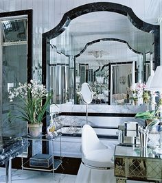 """""""The whole master bath is mirrored—it's like a prism,"""" says Buatta, who also used white marble with black-marble trim. Art Déco dressing table from Lorin Marsh. étagère from Yale R. Burge. Niermann Weeks light fixture in mirror. Lee Jofa Ultrasuede on chair."""